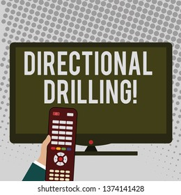 Handwriting text writing Directional Drilling. Concept meaning drilling for oil which the well not drilled vertically Hand Holding Computer Remote Control infront of Blank Wide Color PC Screen.