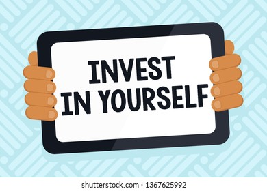 Handwriting text writing Invest In Yourself. Concept meaning learn new things or materials thus making your lot better Color Tablet Smartphone with Blank Screen Handheld from the Back of Gadget.