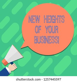 Handwriting text writing New Heights Of Your Business. Concept meaning Achieving goals fast growing up company Hu analysis Hand Holding Megaphone Blank Round Color Speech Bubble photo.