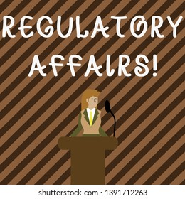 Handwriting text writing Regulatory Affairs. Concept meaning the desire of governments to protect public health Businesswoman Standing Behind Podium Rostrum Speaking on Wireless Microphone.