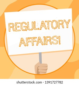 Handwriting text writing Regulatory Affairs. Concept meaning the desire of governments to protect public health Hand Holding Blank White Placard Supported by Handle for Social Awareness.