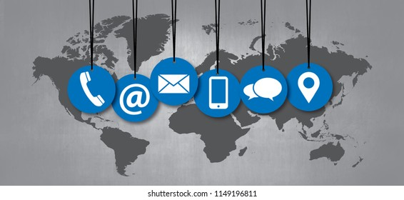 Hanging contact us symbols in front of a world map on school board Social Media network icons call us email app mobile signs fun funny whatsapp likes connect speech bubbles business school multimedia