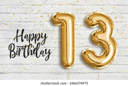 Happy 13th birthday gold foil balloon greeting white wall background. 13 years anniversary logo template- 13th celebrating with confetti. Photo stock.