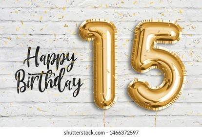 Happy 15th birthday gold foil balloon greeting white wall background. 15 years anniversary logo template- 15th celebrating with confetti. Photo stock.