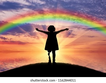A happy child is a disabled girl with a prosthetic leg in the open air on the background of sea sunset and rainbow. The concept of happy children with prosthetic legs