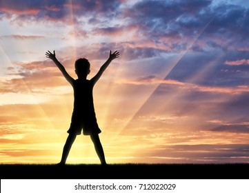 Happy childhood concept. Silhouette of a happy child on the background of the bright sunset
