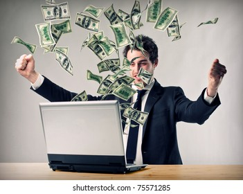 happy man with laptop and money explosion