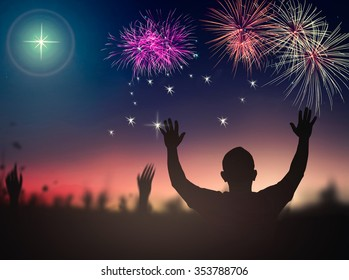 Happy New Year 2019 concept: Silhouette people raising hands for worship God over beautiful fireworks on night background