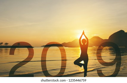 Happy new year card 2019. Silhouette of a girl doing Yoga vrikshasana tree pose on the beach with beautiful sunset and golden sky background, standing as a part of the Number 2019 sign.