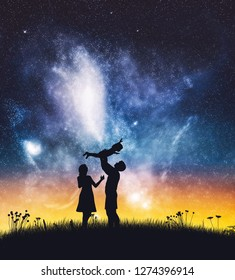 Happy parents with a baby on starry night sky. Joyful family, mother and father.