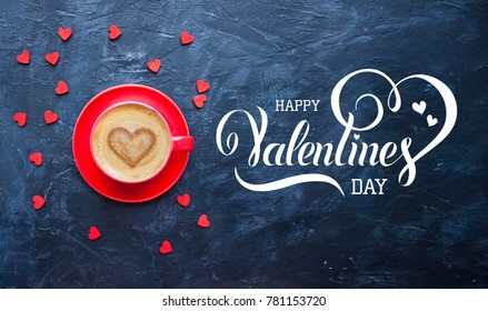 Happy Valentines Day hand lettering inscription. Cup of coffee with heart shape on dark blue background for Valentine's Day greeting card.