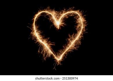 Heart drawn sparklers on black background.