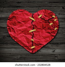Heart repairing therapy as a red crumpled paper shaped as a torn love icon that has been taped together as a metaphor for therapy on old wood also a symbol of medical cardiovascular health .