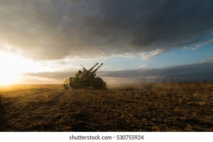 heavy tank in a field with two guns