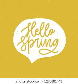 Hello Spring phrase handwritten with elegant cursive font or script inside speech balloon or bubble on yellow background. Springtime seasonal lettering or inscription. Hand drawn  illustration.
