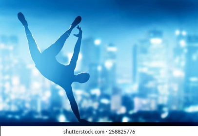 Hip hop, break dance performed by young man in city lights. Nightlife party time