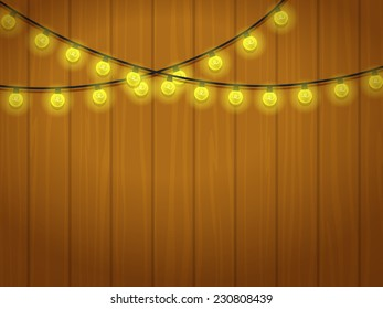 Holiday garland of yellow bulbs on a wooden wall.