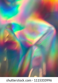 Holographic iridescent gradient wrinkled foil. colorful vivid background.