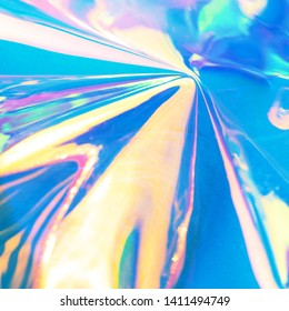 Holographic iridescent surface. Copy space. Bright colorful hologram background. Wrinkled abstract texture with multiple colors. Neon surface