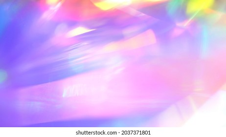 A holographic rainbow unicorn pastel purple pink teal colors abstract background. Optical crystal prism flare beams. Neon light flares