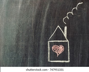Home or love concept. Painted House with Red Heart on a Black Chalkboard.