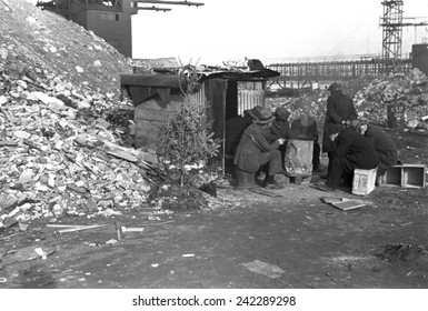 Hooverville at East 12th Street, New York City. Unemployed workers sit on crates by a shack with Christmas tree. January 1938 photo by Russell Lee.