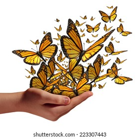Hope and freedom concept as a human hand releasing a group of butterflies as a symbol for education communication and spreading ideas with social marketing isolated on a white background.