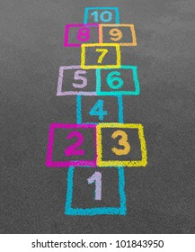 Hopscotch in a schoolyard on an asphalt floor with chalk drawings of numbers and squares as an icon of youth innocence and children playing a fun jumping game at recess or after elementary school.
