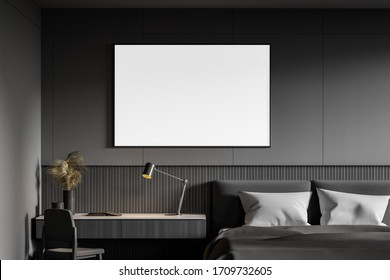 Horizontal mock up poster hanging above table in comfortable master bedroom with king size bed and dark grey walls. 3d rendering