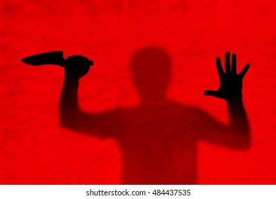 Horror scene of Man and knife behind stained or dirty window glass. Murder or violence concept background
