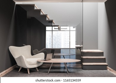 Hotel lobby with white and gray walls, a concrete floor and a gray and wooden staircase. A soft armchair with a round coffee table. A laptop. 3d rendering mock up