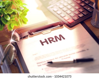 HRM- Text on Clipboard with Office Supplies on Desk. 3d Rendering. Blurred and Toned Illustration.