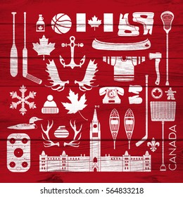 A huge collection of stereotypical Canadian icons on a background of barn board. This group contains hockey sticks, axes, antlers, maple leaves, anchors and other items that represent Canada.