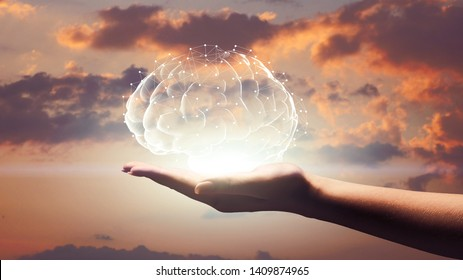 Human brain hologram on female palm, sunset sky background, free space