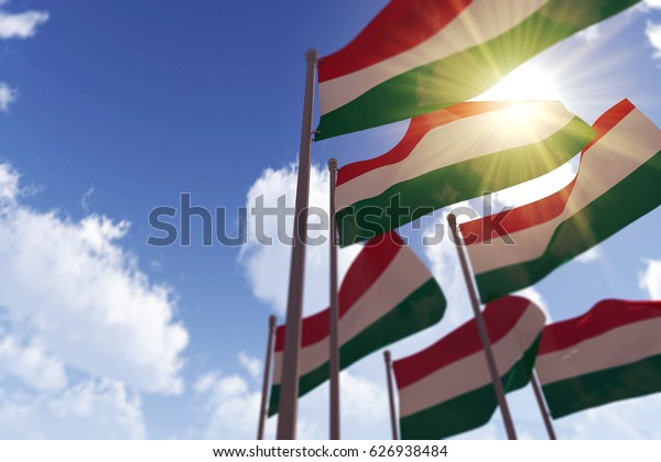 Hungary flags waving in the wind against a blue sky. 3D Rendering