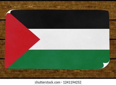 Illustration of a Palestinian flag on the paper pasted on the woody wall