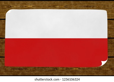 Illustration of a Polish flag on the paper pasted on the woody wall