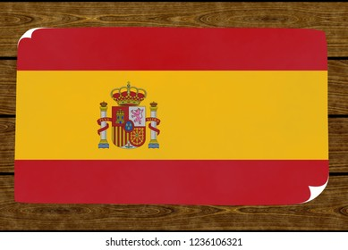 Illustration of a Spanish flag on the paper pasted on the woody wall