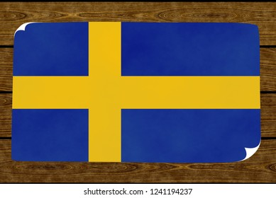 Illustration of a Swedish flag on the paper pasted on the woody wall