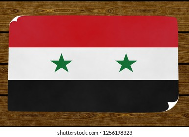 Illustration of a Syrian flag on the paper pasted on the woody wall