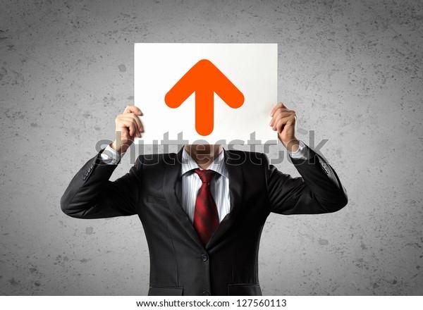 Imagen de hombre sosteniendo el tablero con una foto de flecha