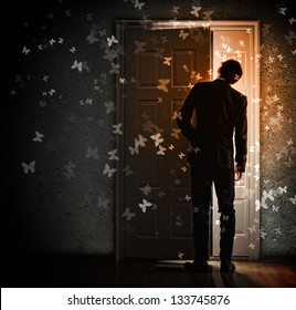 Image of young businessman standing with back opening door