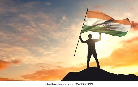 India flag being waved by a man celebrating success at the top of a mountain. 3D Rendering