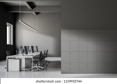 Industrial style office interior with gray walls, a white glossy floor and rows of computer tables standing near white lockers. Business and finance. 3d rendering mock up