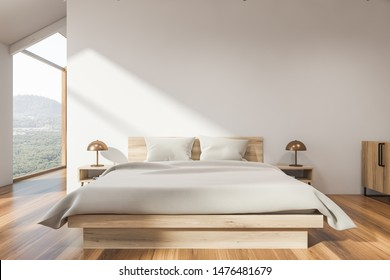 Interior of attic bedroom with white walls, wooden floor, master bed with white blanket and window with mountain view. 3d rendering