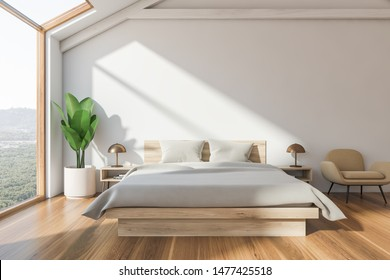 Interior of attic bedroom with white walls, wooden floor, master bed with white blanket, beige armchair and window with mountain view. 3d rendering