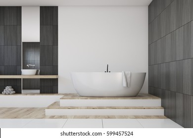 Interior of a bathroom with a vertical mirror hanging on a white and black wall, a white bathtub and a sink. There are steps leading to the tub. 3d rendering. Mock up
