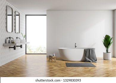 Interior of bathroom with white and tiled walls, wooden floor, white bathtub with towel on it and double sink standing on white countertop with two vertical mirrors. 3d rendering