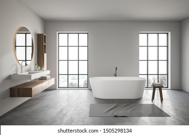 Interior of comfortable bathroom with white walls, concrete floor, large windows, bathtub and sink with round mirror above it. 3d rendering