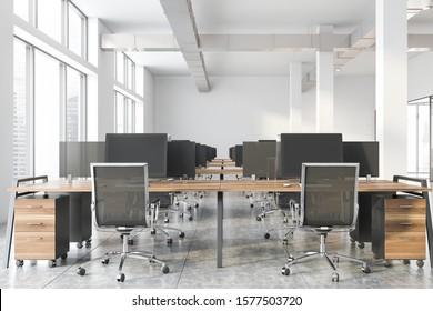 Interior of industrial style office with white walls, concrete floor, windows with cityscape and row of wooden computer tables with black chairs. 3d rendering